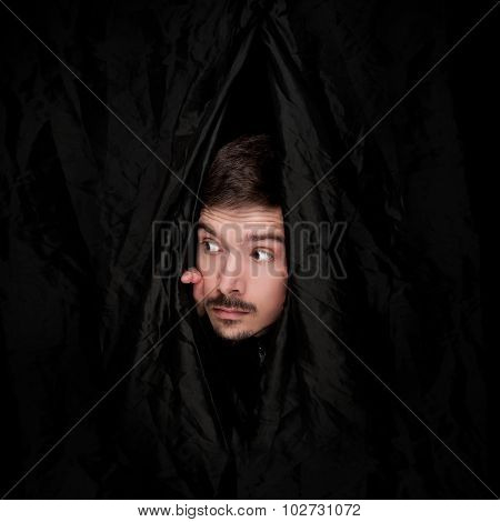 Young men with black hair peeking from black curtain