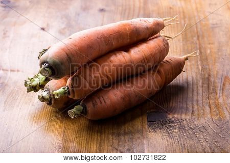 Fresh homemade carrot loose on a wooden table.