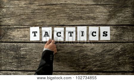 Overhead View Of Strategic Business Partner Assembling The Word Tactics