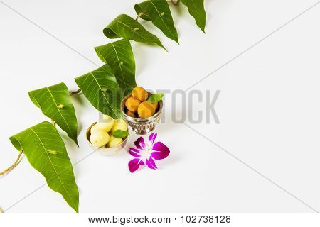 arland of mango leaves with indian sweet pedha and orchid flower . It is auspicious in hindu religio