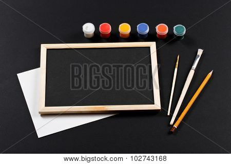 Wooden Frame With Black Field And With Brushes And Set Of Gouache Of Different Colors On Black Paper