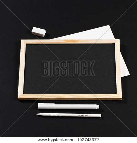 Wooden Frame With Black Field With Marker And White Pencil And Eraser On Black Paper. Mockup. Real P