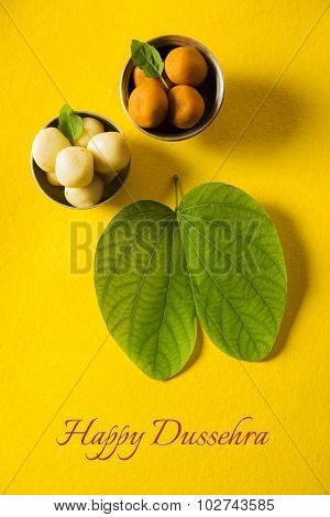 indian festival dussehra, showing golden leaf with traditional indian sweets pedha in silver bowl on