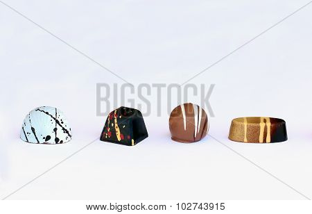 Four chocolate bonbons on white background