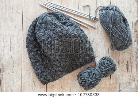 wool grey hat, knitting needles and yarn on wooden background