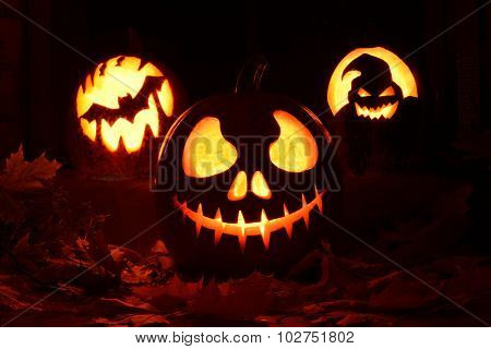 Three evil pumpkins on a table with leaves and candles