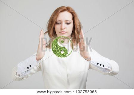 Young woman holding green plant ying yang symbol