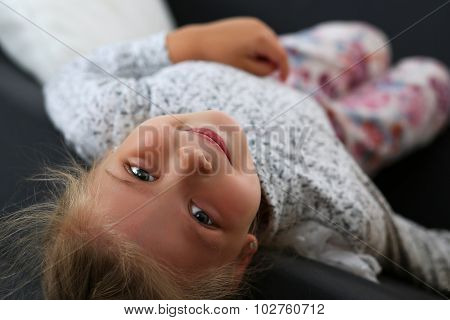Smiling Little Blonde Girl Lying On Couch