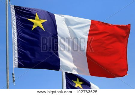Acadian Flag with Blue Sky Background