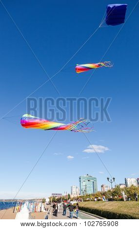 Colorful Kites Flying Against A Blue Sky On The City Embankment In Samara, Russia