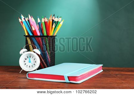 Notebook, metal cup of crayons and alarm clock on desk on green chalkboard background