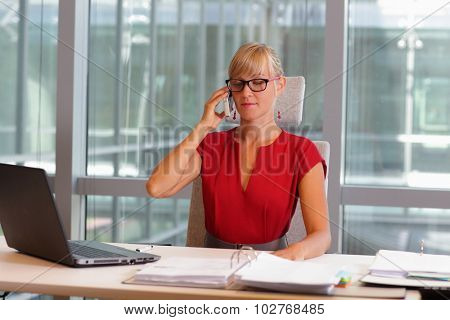 caucasian business woman in eyeglasses on phone in her office