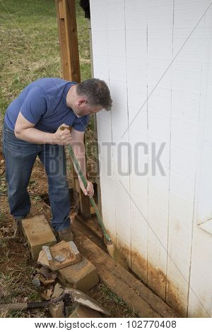 Man sweeping dirt with broom