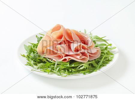 plate of fresh arugula leaves with sliced ham on white background