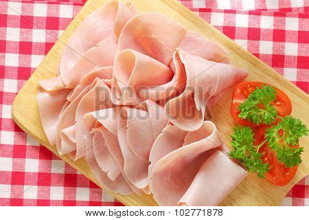 thinly sliced ham on wooden cutting board and checkered table cloth