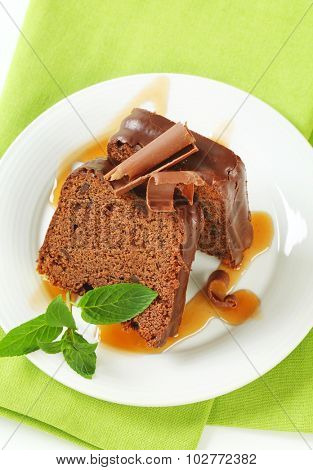 slices of chocolate cake with mint, chocolate shavings and caramel topping on white plate and green napkin