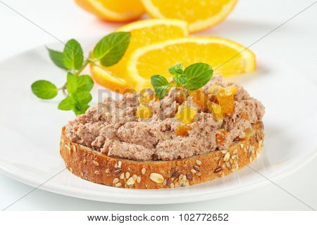 slice of bread with meat spread and pieces of orange on white plate
