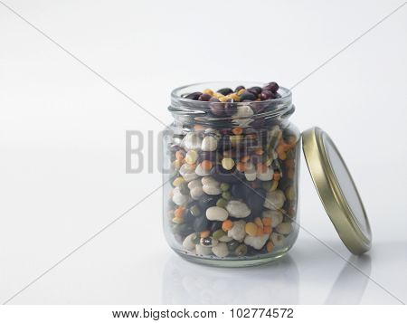 Mix bean of black eye peas, mung bean, adzuki beans, soy beans, black beans and red kidney beans in a mason jar over white background
