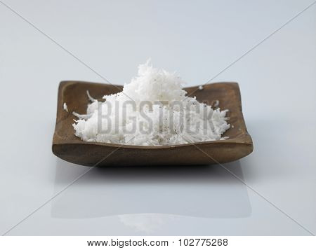 small wooden bowl filled with shredded coconut on a white background.