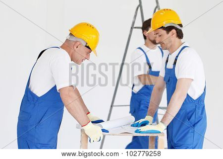 workmen looking at house design