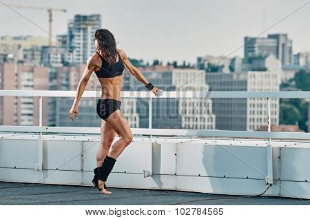 Fitness woman stretching house-top