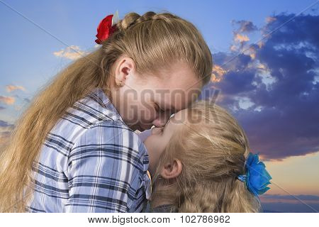 Two sisters embracing and kissing