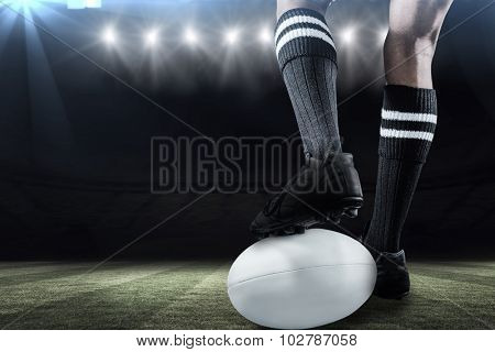Sportsman keeping leg on ball while playing rugby against rugby stadium