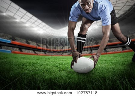 Portrait of sportsman bending and holding ball while playing rugby against rugby stadium