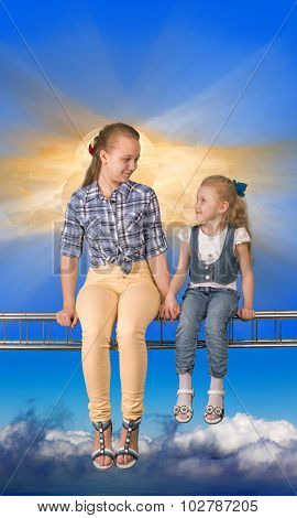 Two girls sitting on the beam