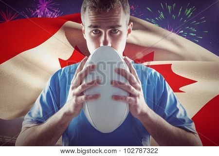 Rugby player holding a rugby ball against fireworks exploding over football stadium