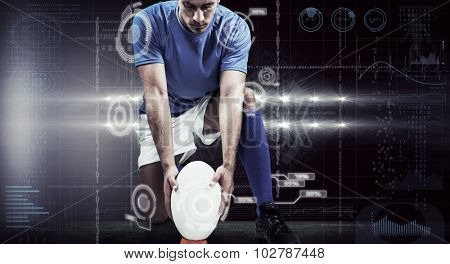 Full length of rugby player placing ball against spotlights