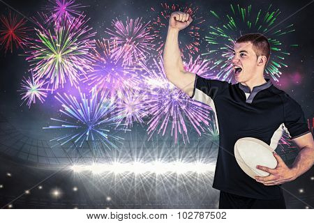 A rugby player gesturing victory against fireworks exploding over football stadium