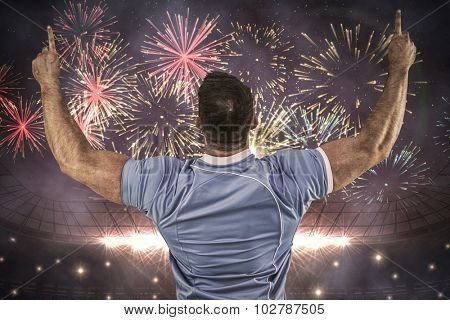 Rugby player cheering and pointing against fireworks exploding over football stadium
