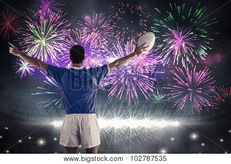 Rugby player about to throw a rugby ball against fireworks exploding over football stadium