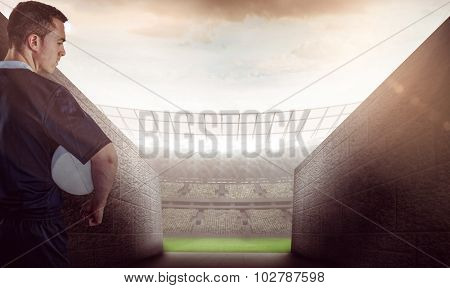 Rugby player gesturing with hands against rugby stadium