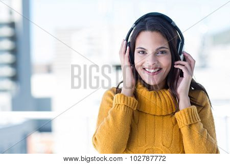 Pretty woman listening music through headphones outside