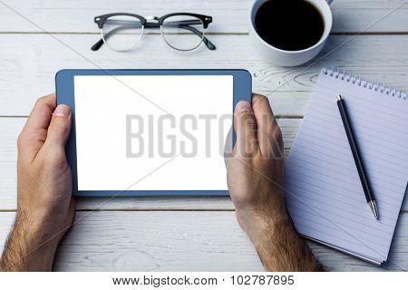 Cropped image of person holding tablet computer next to various objects at desk