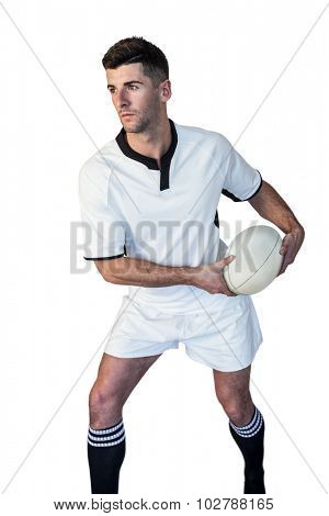 Rugby player defending the ball over white background