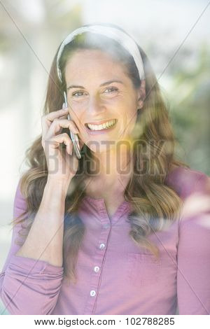 Portrait of happy pregnant woman talking on cellphone by window at home