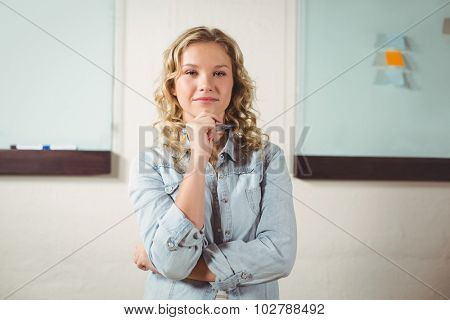 Portrait of beautiful confident woman with hand on chin standing in office