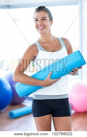 Beautiful woman smiling while holding yoga mat in fitness studio