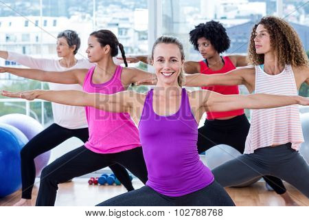Group of women exercising with arms outstretched in fitness studio