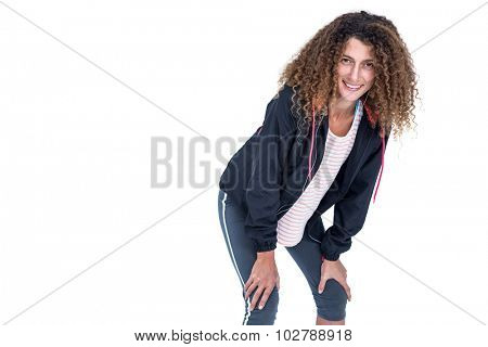 Portrait of happy young woman bending with hand on knee against white background