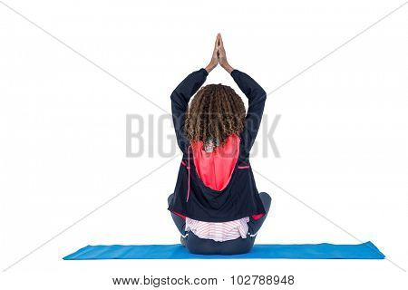 Rear view of woman practicing yoga on exercise mat against white background