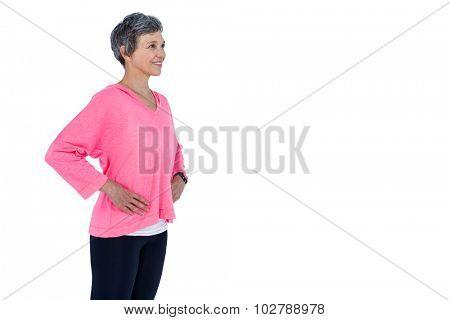 Mature woman with hand on hip standing against white background