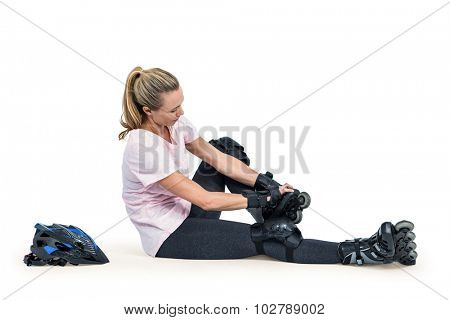 Sporty woman wearing inline skates over white background