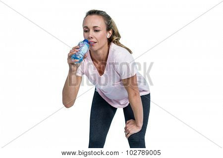 Tired sporty woman bending and drinking water over white background