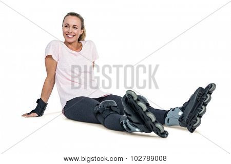 Happy female inline skater relaxing over white background