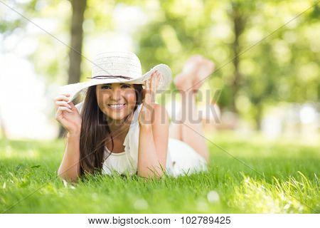 Portrait of happy woman holding sun hat while lying on grassland in park