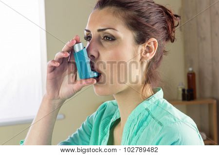 Close-up of woman using asthma inhaler at home